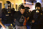 Police arrest a demonstrator during clashes demand the resignation of Gov. Ricardo Rossello in San Juan, Puerto Rico, Monday, July 22, 2019.  Protesters are demanding Gov. Ricardo Rossello step down following the leak of an offensive, obscenity-laden online chat between him and his advisers that triggered the crisis.   (AP Photo/Carlos Giusti)