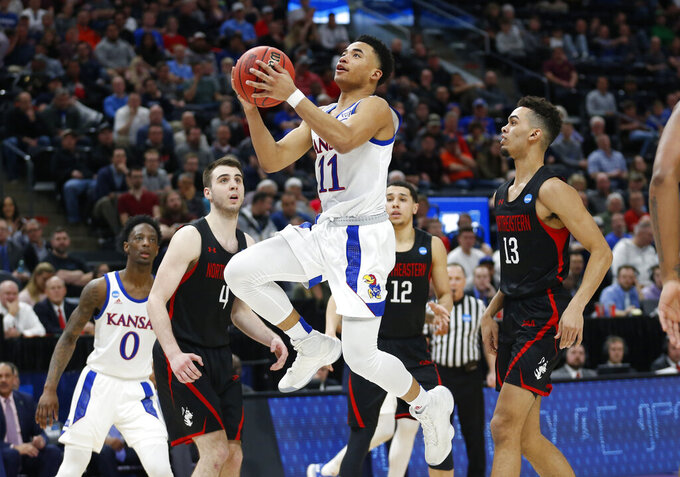 Kansas guard Devon Dotson (11) goes to the basket as Northeastern guard Myles Franklin (13) looks on in the second half during a first round men's college basketball game in the NCAA Tournament, Thursday, March 21, 2019, in Salt Lake City. (AP Photo/Rick Bowmer)