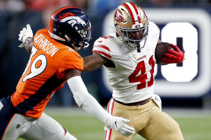 San Francisco 49ers running back Jeff Wilson Jr. (41) tries to avoid the tackle of Denver Broncos cornerback Trey Johnson (39) during the second half of an NFL preseason football game, Monday, Aug. 19, 2019, in Denver. (AP Photo/David Zalubowski)