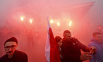 Marchers burn flares as they take part in the annual March of Independence organized by far right activists to celebrate 101 years of Poland's independence, in Warsaw, Poland, Monday, Nov. 11, 2019. (AP Photo/Czarek Sokolowski)
