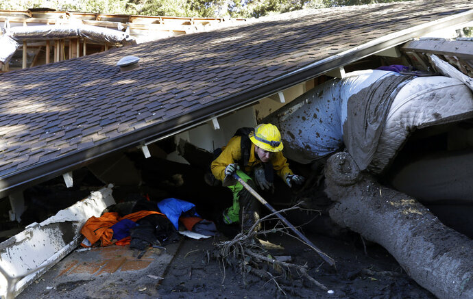 Colette Layton, bottom, of the Atascadero Fire Dept, searches a home Saturday, Jan. 13, 2018, in Montecito, Calif.  Most of the people of Montecito, a town usually known for its serenity and luxury, were under orders to stay out of town as gas and power were expected to be shut off Saturday for repairs. (AP Photo/Marcio Jose Sanchez)