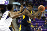 TCU center Kevin Samuel (21) defends as West Virginia forward Andrew Gordon (12) looks to make a pass in the first half of an NCAA college basketball game, Tuesday, Jan. 15, 2019, in Fort Worth, Texas. (AP Photo/Tony Gutierrez)