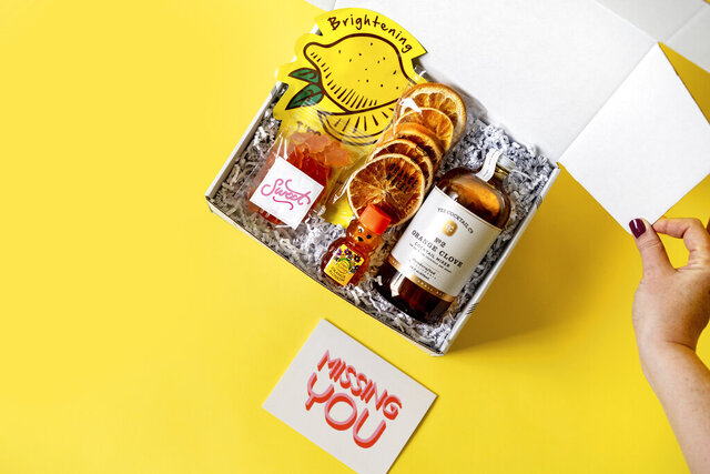 This product image shows citrus items in a gift box from HappyBoxStore.com. It's filled with grapefruit gummy bears, orange blossom honey, a tangerine clove cocktail mixer, a lemon hydrating sheet face mask and more. (Happy Box via AP)