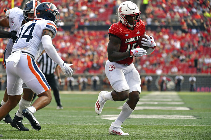 Louisville running back Jalen Mitchell (15) runs past the defense of Virginia defensive back Antonio Clary (14) to cross the goal line for a touchdown during the second half of an NCAA college football game in Louisville, Ky., Saturday, Oct. 9, 2021. Virginia won 34-33. (AP Photo/Timothy D. Easley)