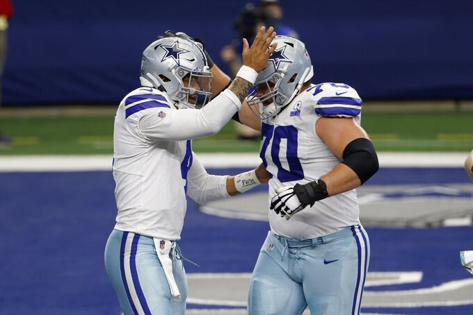 Dallas Cowboys quarterback Dak Prescott (4) and Zack Martin (70) celebrate Prescott's two-point conversion on a short run in the second half of an NFL football game against the Cleveland Browns in Arlington, Texas, Sunday, Oct. 4, 2020. (AP Photo/Ron Jenkins)