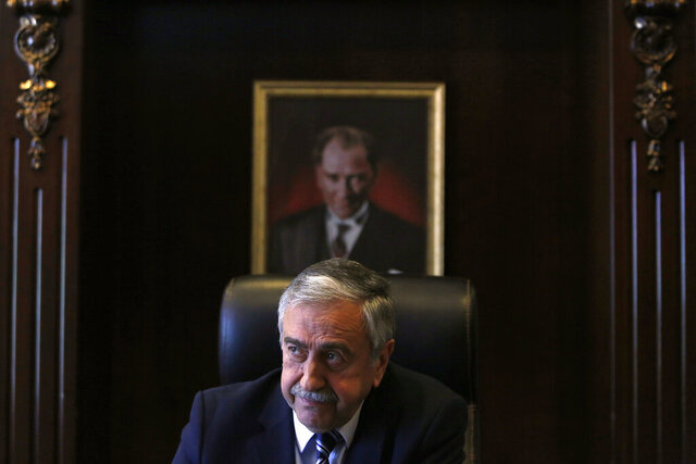 FILE - In this Monday, April 4, 2016 file photo, Turkish Cypriot leader Mustafa Akinci is seen at his office in front of the portrait of the Turkish Republic founder Kemal Ataturk, during an interview for the Associated Press in the Turkish breakaway north part of the divided capital Nicosia in this ethnically Mediterranean island of Cyprus. Turkish Cypriots vote on Sunday Oct. 18, 2020 in a leadership runoff that could decide if they want to retain more control over their own affairs or steer even closer to an increasingly domineering Turkey. (AP Photo/Petros Karadjias, File)