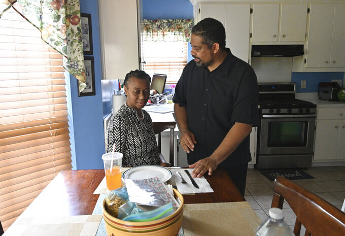 Robert Reid prepares snacks for his wife Kim Reid, who was diagnosed with early-onset Alzheimer's, at their home in Hampton on Thursday, June 10, 2021.  (Hyosub Shin/Atlanta Journal-Constitution via AP)