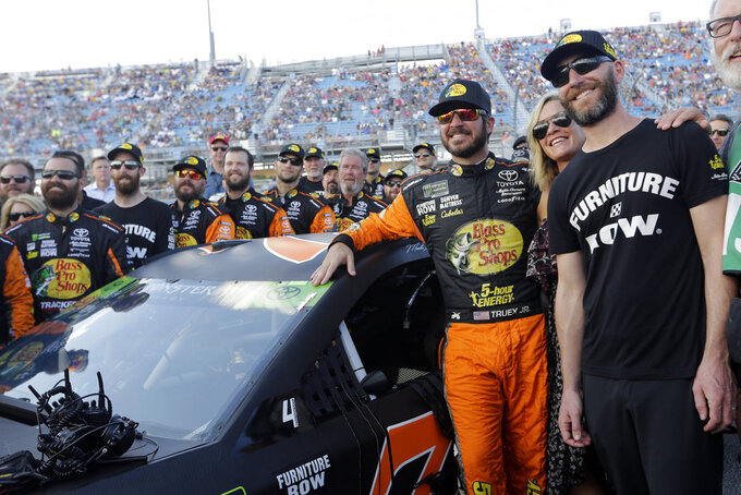 Martin Truex Jr., left, stands with his girlfriend Sherry Pollex, center, and his crew before the NASCAR Series Championship auto race at the Homestead-Miami Speedway, Sunday, Nov. 18, 2018, in Homestead, Fla. (AP Photo/Lynne Sladky)