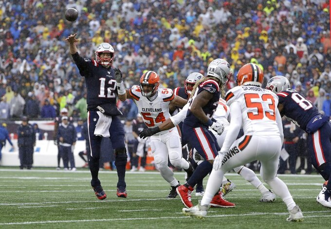 New England Patriots quarterback Tom Brady, left, passes under pressure from Cleveland Browns defensive end Olivier Vernon (54) in the first half of an NFL football game, Sunday, Oct. 27, 2019, in Foxborough, Mass. (AP Photo/Steven Senne)