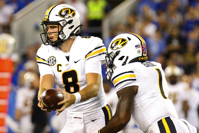 Missouri quarterback Connor Bazelak (8) hands the ball off to running back Tyler Badie (1) during the first half of an NCAA college football game against Kentucky in Lexington, Ky., Saturday, Sept. 11, 2021. (AP Photo/Michael Clubb)