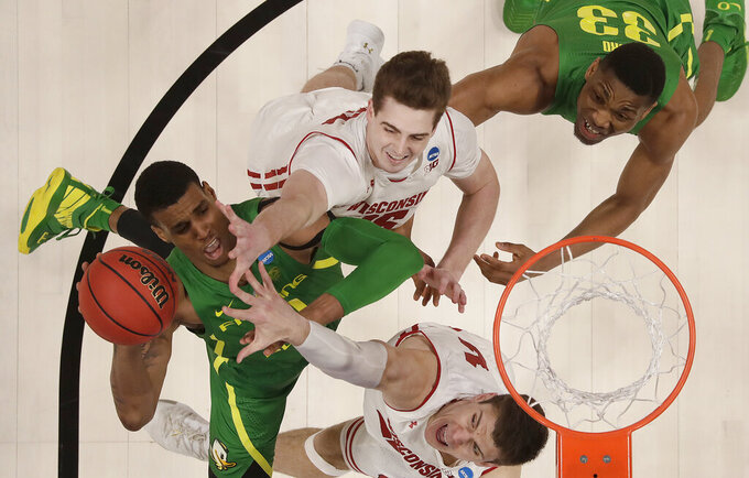 Oregon forward Kenny Wooten, left, shoots between Wisconsin forward Nate Reuvers, center top, and forward Ethan Happ during the second half of a first round men's college basketball game in the NCAA Tournament, Friday, March 22, 2019, in San Jose, Calif. (AP Photo/Ben Margot)