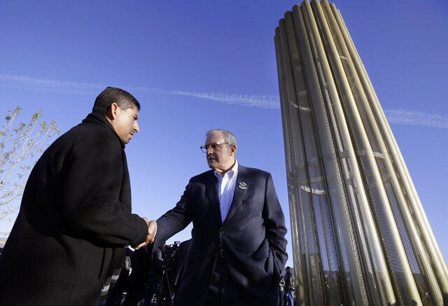 El Paso, Texas Mayor Dee Margo shakes hands with Walmart manager Robert Evans during the dedication ceremony for the Grand Candela, a 30-foot tall golden obelisk at Walmart in El Paso, Texas on Saturday, Nov. 23, 2019.   The memorial was unveiled Saturday honoring the 22 people who were killed in an Aug. 3 shooting at the Walmart. (Mark Lambie /The El Paso Times via AP)