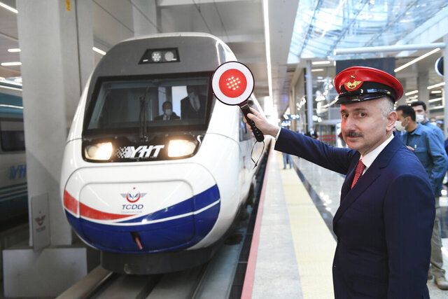 In this photo provided by Turkey's Transportation Ministry, Minister Adil Karaismailoglu poses for images as a train departs for Istanbul from Ankara's train station, Turkey, Thursday, May 28, 2020. Turkey has resumed limited intercity train operations after a two-month suspension as the country eases restrictions imposed to contain the coronavirus outbreak.(Transportation Ministry via AP )