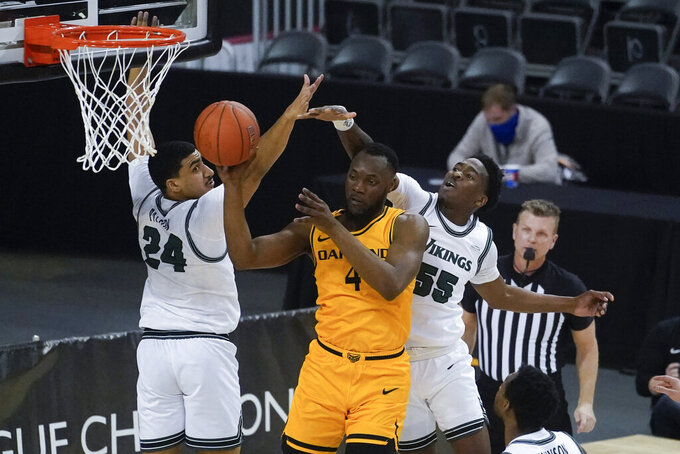 Oakland's Daniel Oladapo (4) makes a pass against Cleveland State's Torrey Patton (24) and D'Moi Hodge (55) during the first half of an NCAA college basketball game in the men's Horizon League conference tournament championship game, Tuesday, March 9, 2021, in Indianapolis. (AP Photo/Darron Cummings)