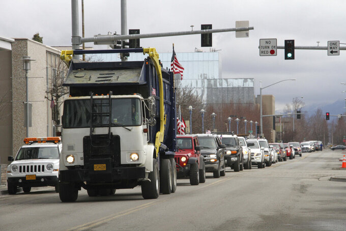 More than 80 vehicles take part in a caravan through downtown Anchorage, Alaska, Wednesday, April 22, 2020, with participants urging local and state leaders to open up businesses shuttered temporarily while residents were told to stay home. The state will allow some businesses to open Friday, followed by some in Anchorage next Monday (AP Photo/Mark Thiessen)