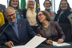 Washington Gov. Jay Inslee, left, and Oregon Gov. Kate Brown react as they celebrate with supporters after signing a memorandum of intent to replace the Interstate 5 bridge in Vancouver, Wash., Monday, Nov. 18, 2019. (Nathan Howard/The Columbian via AP)