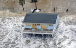 FILE - In this Sept. 12, 2008, file photo, a boarded-up home sits along the beach as Hurricane Ike approaches in Galveston, Texas. The Ike Dike is a proposed coastal barrier that would protect the Houston-Galveston region, including Galveston Bay, from hurricane storm surge. The project was conceived by Bill Merrell, a professor in the Marine Sciences Department at Texas A&M University at Galveston and a former president of the school, in response to the extensive surge damage caused by Hurricane Ike in September of 2008. (AP Photo/David J. Phillip, File)