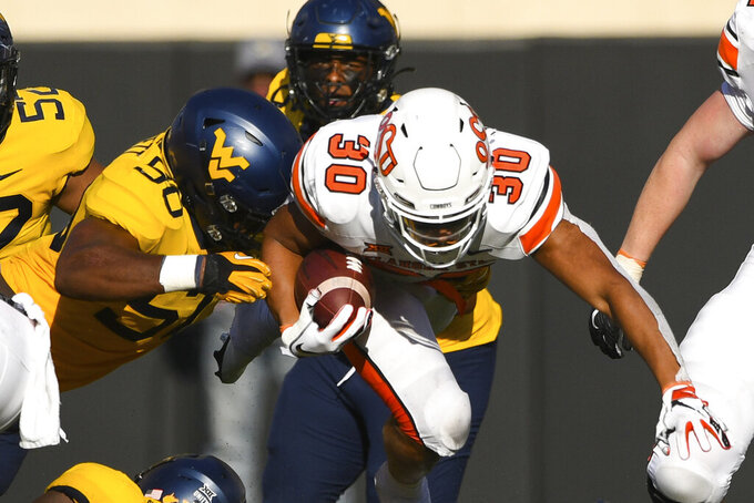 West Virginia defensive end Jared Bartlett (50) reaches for Oklahoma State running back Chuba Hubbard (30) during the second half of an NCAA college football game Saturday, Sept. 26, 2020, in Stillwater, Okla. (AP Photo/Brody Schmidt)