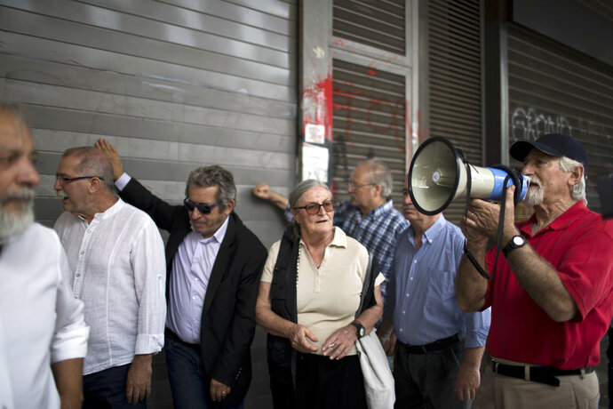 Pensioners rattle the shutters of the main entrance of the Labor ministry during a protest in central Athens, on Wednesday, May 16, 2018. The government has repeatedly cut pensions as part of the country's three international bailouts. More cuts are planned in 2019.(AP Photo/Petros Giannakouris)
