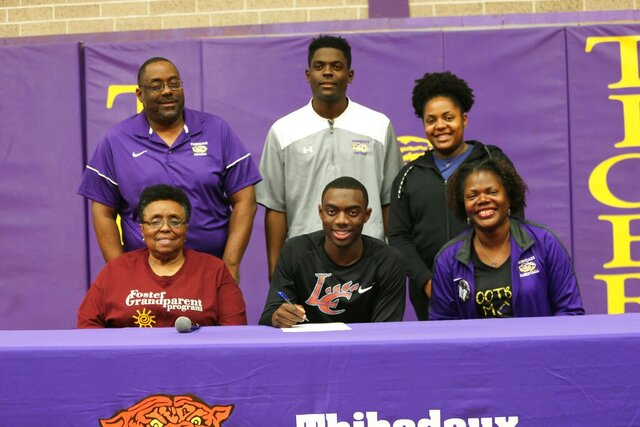 In this Feb. 6, 2020, photo, Thibodaux High School senior Tyren Young, seated in the middle, poses with his family as he has accepted a college scholarship to play football at Louisiana College during National Signing Day, in Thibodaux, La. (Chris Singleton/The Courier via AP)