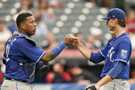 Kansas City Royals starting pitcher Brady Singer, right, celebrates with catcher Salvador Perez after they defeated the Cleveland Indians in the first baseball game of a doubleheader, Monday, Sept. 20, 2021, in Cleveland. (AP Photo/Tony Dejak)