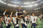 FILE- In this Jan. 26, 1986, file photo, Chicago Bears head coach Mike Ditka is carried off the field by Steve McMichael, left, and William Perry after the Bears defeated the New England Patriots 46-10 in Super Bowl XX in New Orleans.  (AP Photo/Phil Sandlin, File)