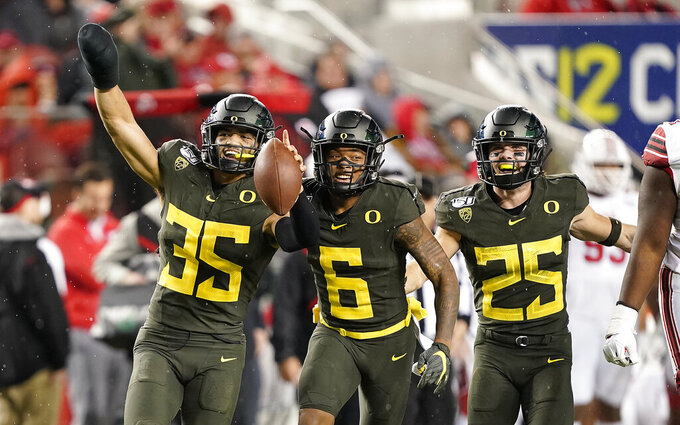 Oregon linebacker Troy Dye (35) celebrates with teammates Deommodore Lenoir (6) and Brady Breeze (25) after Dye intercepted a Utah pass during the second half of an NCAA college football game for the Pac-12 Conference championship in Santa Clara, Calif., Friday, Dec. 6, 2018. Oregon won 37-15. (AP Photo/Tony Avelar)