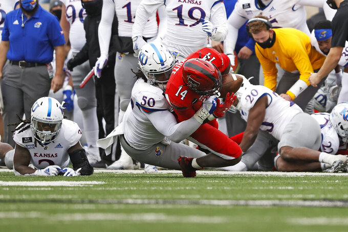 Kansas' Marcus Harris (50) forces a fumble while tackling Texas Tech's Xavier White (14) during the second half of an NCAA college football game Saturday, Dec. 5, 2020, in Lubbock, Texas. (AP Photo/Brad Tollefson)