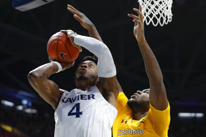 Xavier's Tyrique Jones (4) shoots against Lipscomb's Ahsan Asadullah, right, during the first half of an NCAA college basketball game, Saturday, Nov. 30, 2019, in Cincinnati. (AP Photo/John Minchillo)