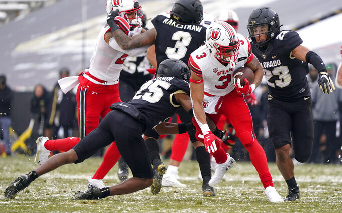 Utah running back Micah Bernard, center, is stopped by Colorado cornerback Mekhi Blackmon, left, and safety Isaiah Lewis in the second half of an NCAA college football game Saturday, Dec. 12, 2020, in Boulder, Colo. Utah won 38-21. (AP Photo/David Zalubowski)