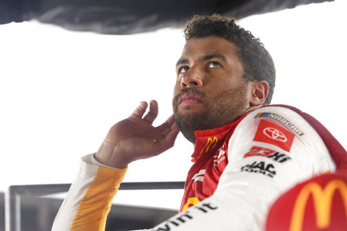 Bubba Wallace waits out a rain delay before winning a NASCAR Cup series auto race Monday, Oct. 4, 2021, in Talladega, Ala. (AP Photo/John Amis)