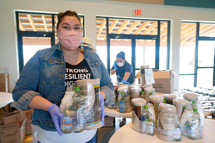 In this May, 2020, photo provided by the Thunder Valley Community Development Corporation, DeCora Hawk poses for a photo as community engagement director at the Thunder Valley CDC on the Pine Ridge Indian Reservation. Hawk works to organize cleaning supplies that were sent to elderly residents on the reservation. (Thunder Valley CDC Staff via AP)