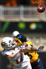 West Virginia Tykee Smith (23) shoves Oklahoma State wide receiver Dillon Stoner (17) during an NCAA college football game Saturday, Sept. 26, 2020, in Stillwater, Okla. (AP Photo/Brody Schmidt)