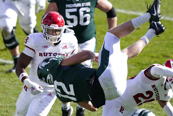 Michigan State quarterback Rocky Lombardi (12) jumps over Rutgers defensive back Lawrence Stevens (29) during the second half of an NCAA college football game, Saturday, Oct. 24, 2020, in East Lansing, Mich. (AP Photo/Carlos Osorio)