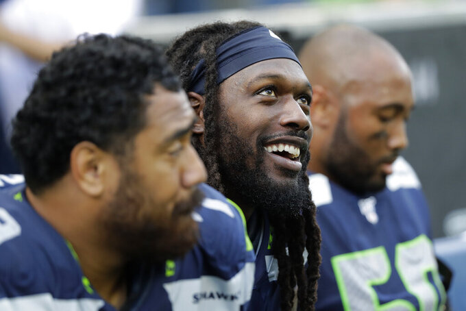 Seattle Seahawks defensive end Jadeveon Clowney, center, sits on the bench with teammates late in the second half of an NFL football game against the Cincinnati Bengals, Sunday, Sept. 8, 2019, in Seattle. (AP Photo/John Froschauer)