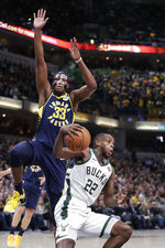 Milwaukee Bucks forward Khris Middleton (22) fakes under Indiana Pacers center Myles Turner (33) during the second half of an NBA basketball game in Indianapolis, Wednesday, Feb. 13, 2019. The Bucks defeated the Pacers 106-97. (AP Photo/Michael Conroy)