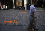 A woman follows physical distancing arrows as she walks on a shopping street, during a partial lifting of coronavirus, COVID-19, regulations in Halle, Belgium, Wednesday, June 24, 2020. (AP Photo/Virginia Mayo)