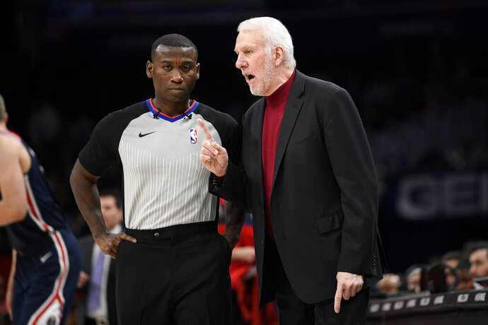 San Antonio Spurs coach Gregg Popovich, right, gestures next to an official during the second half of the team's NBA basketball game against the Washington Wizards on Wednesday, Nov. 20, 2019, in Washington. The Wizards won 138-132. (AP Photo/Nick Wass)