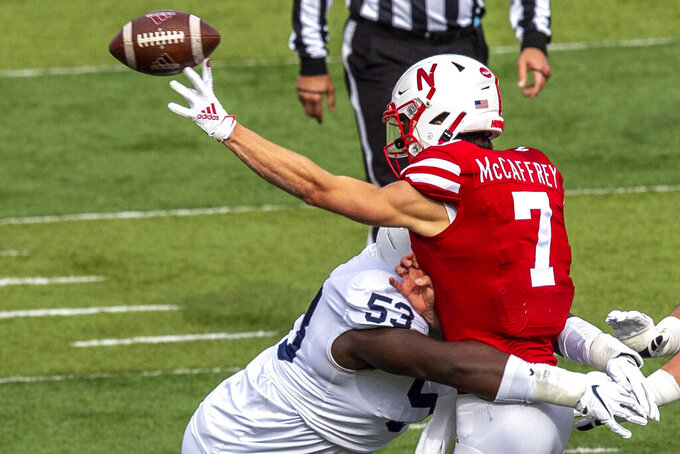 Nebraska's Luke McCaffrey (7) throws a complete pass while getting hit by Penn State's Fred Hansard late in the second quarter of an NCAA college football game in Lincoln, Neb., Saturday, Nov. 14, 2020. (Chris Machian/Omaha World-Herald via AP)