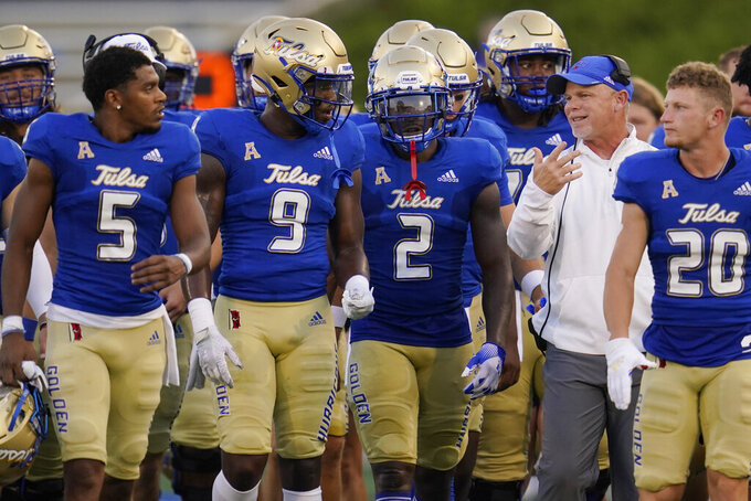 Tulsa head coach Philip Montgomery talks with his players during the first half of the team's NCAA college football game against UC Davis, Thursday, Sept. 2, 2021, in Tulsa, Okla. (AP Photo/Sue Ogrocki)