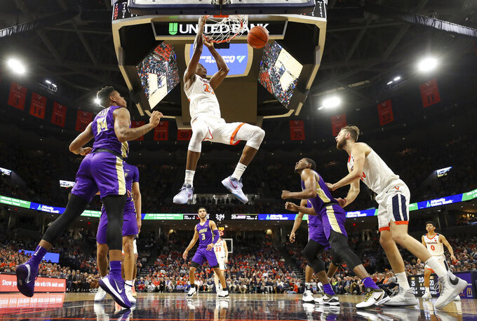 Virginia forward Mamadi Diakite (25) dunks between James Madison defenders during an NCAA college basketball game in Charlottesville, Va., Sunday, Nov. 10, 2019. Virginia won 65-34. (AP Photo/Andrew Shurtleff)