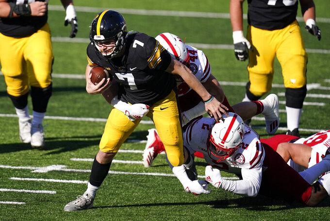 Iowa quarterback Spencer Petras (7) is tackled by Nebraska linebacker Caleb Tannor (2) and linebacker Garrett Nelson (44) during the first half of an NCAA college football game, Friday, Nov. 27, 2020, in Iowa City, Iowa. (AP Photo/Charlie Neibergall)