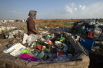 A waste picker walks past collected material for recycling in the Vosloorus Township near Johannesburg, South Africa, Tuesday, Oct. 27, 2020. More than 2 million jobs have been lost during the economic downturn caused by the pandemic in South Africa, a country of 60 million people.(AP Photo/Themba Hadebe)