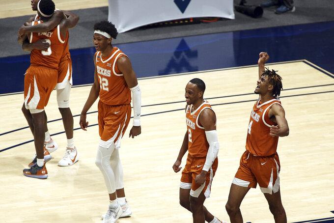 Texas forward Kai Jones (22), guard Matt Coleman III (2) and forward Greg Brown (4) celebrate after an NCAA college basketball game against West Virginia, Saturday, Jan. 9, 2021, in Morgantown, W.Va. (AP Photo/Kathleen Batten)