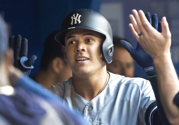 New York Yankees' Gio Urshela celebrates with teammates in the dugout after hitting a two-run home run against the Toronto Blue Jays during the first inning of a baseball game Thursday, Aug. 8, 2019, in Toronto. (Fred Thornhill/The Canadian Press via AP)
