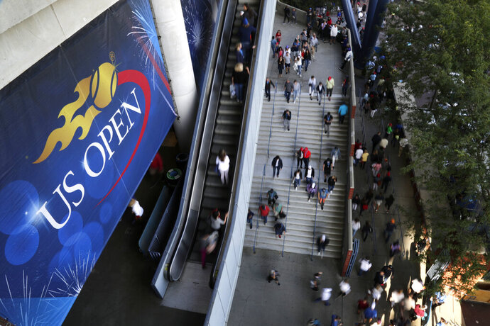 """FILE - In this Sept. 3, 2017, file photo, tennis fans move in and out of Arthur Ashe Stadium during the fourth round of the U.S. Open tennis tournament in New York. As coronavirus cases spike in other parts of the country a month before the U.S. Open is supposed to start in New York, the U.S. Tennis Association said Friday, July 31, 2020, it """"continues its plans"""" to hold its marquee event and another tournament beforehand. (AP Photo/Frank Franklin II, File)"""