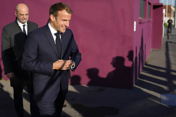 French President Emmanuel Macron, followed by French Education Minister Jean-Michel Blanquer arrive in Tremblay-en-France, outside Paris, Thursday, Oct.14, 2021. French President Emmanuel Macron will promote sports ahead of the 2024 Olympic Games in Paris. (AP Photo/Francois Mori, Pool)