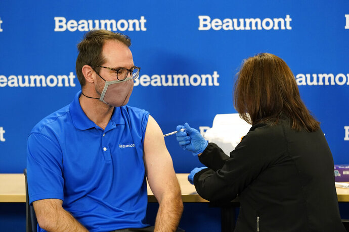 Dr. Nick Gilpin receives his second Pfizer-BioNTech COVID-19 vaccine shot from registered nurse Susan Grant at Beaumont Health in Southfield, Mich., Tuesday, Jan. 5, 2021. (AP Photo/Paul Sancya)