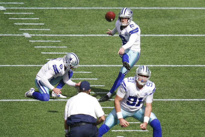 Dallas Cowboys kicker Greg Zuerlein (2) kicks as Chris Jones holds during warmups before an NFL football game against the Seattle Seahawks, Sunday, Sept. 27, 2020, in Seattle. (AP Photo/Elaine Thompson)
