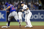 San Diego Padres third baseman Manny Machado, right, throws to first after forcing out Chicago Cubs' Kyle Schwarber, left, at second during the fifth inning of a baseball game Tuesday, Sept. 10, 2019, in San Diego. Anthony Rizzo was safe at first. (AP Photo/Gregory Bull)